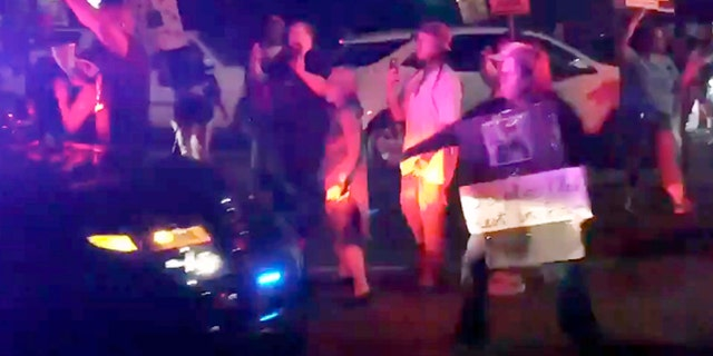 This March 31, 2018 photo made from video by Guy Danilowitz shows Wanda Cleveland moments before being struck by a Sacramento County Sheriff's patrol vehicle during a demonstration over the shooting of Stephon Clark.
