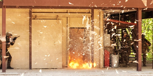 Special operations soldiers stand clear as they blow a door open to demonstrate how they clear buildings during a training exercise.