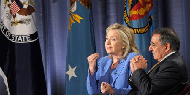 Secretary of State Hillary Clinton, accompanied by Defense Secretary Leon Panetta, speaks during an event at the National Defense University in Washington, D.C., Aug. 16.