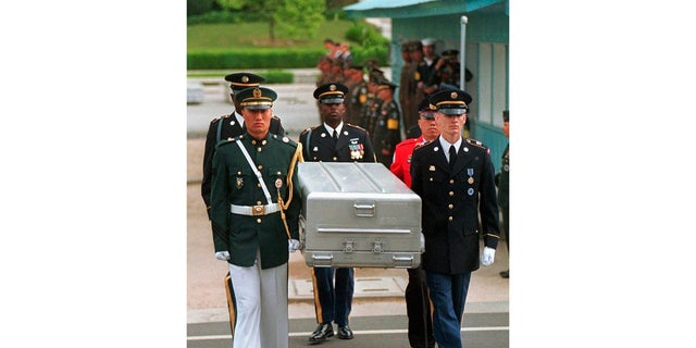 In this May 14, 1999, file photo, U.N. honor guards carry a coffin containing the remains of the American soldiers after it was returned from North Korea at the border village of Panmunjom, South Korea.