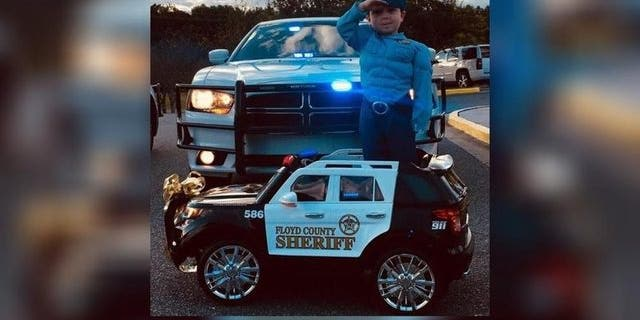 Three-year-old Cohen standing at attention in his electric toy police car.