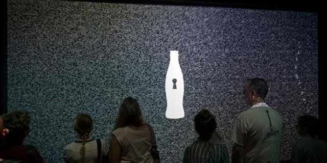 """Aug. 9, 2013: A tour group waits for an interactive experience to begin before entering the vault chamber containing the """"secret recipe"""" for Coca-Cola at the World of Coca-Cola museum, in Atlanta."""
