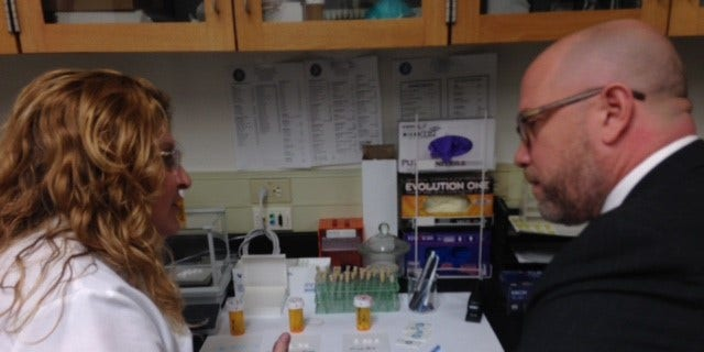 Forensic scientist Deborah Cole shows a drug sample test to New Jersey Attorney General Christopher Porrino