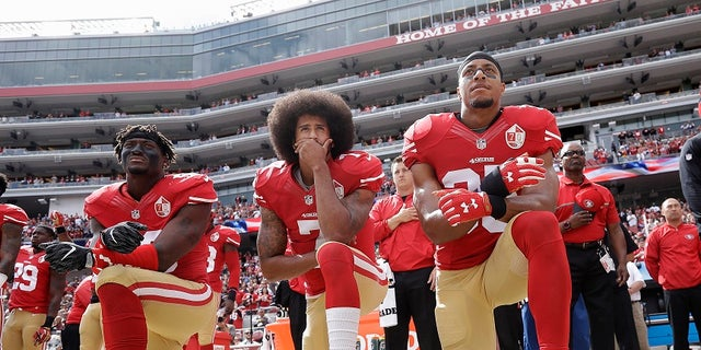 Former San Francisco 49ers quarterback Colin Kaepernick, who has not been signed by any team in the NFL, is seen here kneeling during the national anthem.
