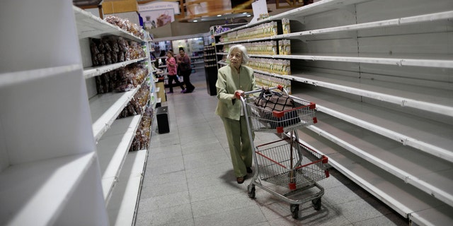 An elderly woman walks through a supermarket in Caracas, Venezuela.