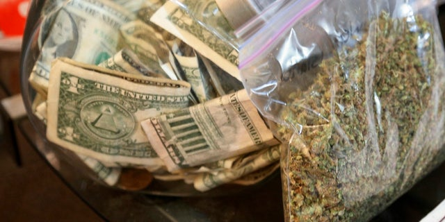 A bag of marijuana being prepared for sale sits next to a money jar at BotanaCare in Northglenn, Colorado.