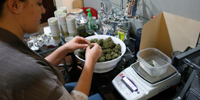 Dec. 31, 2013: Danielle Hackett prepares marijuana buds for sale at BotanaCare in Northglenn, Colorado.