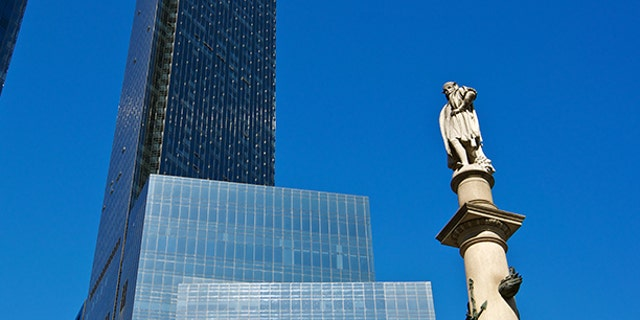 """A cityscape view of the 1892 completed monument to Christopher Columbus, located in Columbus Circle at W.59th Street alongside of Broadway to the West. In the background is the 1990's completed world headquarters of the Time Warner Corporation, it's twin towers dominate the skyline in Upper Midtown Manhattan, New York City."""