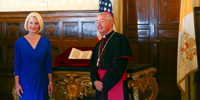 U.S. Ambassador Callista Gingrich, left, is photographed with Archbishop Jean-Louis Brugues on the occasion of the presentation to the Vatican of an authentic 15th Century copy of a letter written by Christopher Columbus, seen at center. Thursday, June 14, 2018. The United States is returning to the Vatican Library a letter written by Christopher Columbus in 1493 announcing his discovery of the New World that was stolen and replaced with a forgery. (Tony Gentile/Pool Photo via AP)