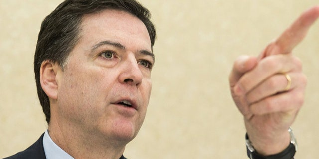 FBI Director James B. Comey takes a question during a news conference on the release of the 9/11 Review Commission report in Washington March 25, 2015. The FBI needs to strengthen its intelligence programs and information sharing to counter the diverse and fast-moving national threats that have evolved since the Sept. 11, 2001, attacks, the congressional commission said on Wednesday. REUTERS/Joshua Roberts