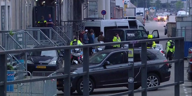 In this image taken from video people and security stand around a van in Rotterdam, Wednesday Aug. 23, 2017, after a concert by an American rock band was cancelled Wednesday night following a threat, the city's mayor said.