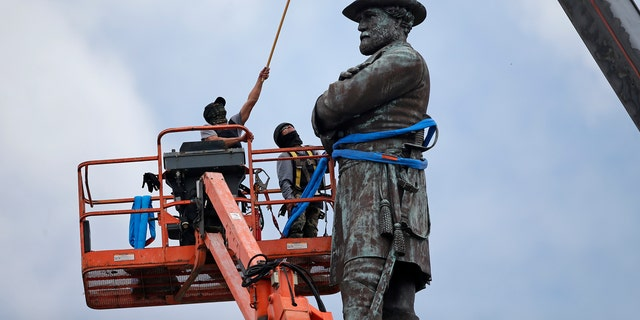 n this Friday, May 19, 2017, file photo, workers prepare to take down the statue of former Confederate Gen. Robert E. Lee, which stands over 100 feet tall, in Lee Circle in New Orleans.