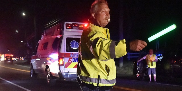 A first responder directs traffic as emergency personnel work the scene of an explosion in North Haven, Conn.