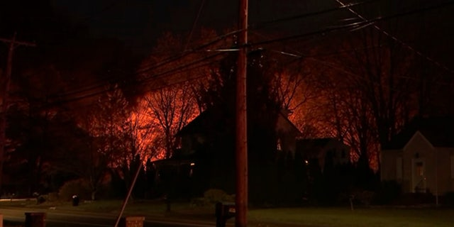 A fire can be seen burning behind a house in North Haven, Conn.