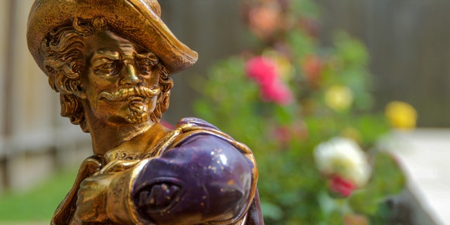 A statue of a conquistador is placed in a rose garden.