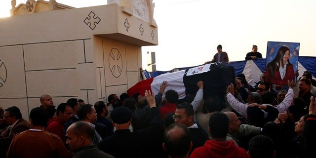 The body of one of the victims from Sunday's bombing of Cairo's main Coptic Cathedral is carried to be buried at the Mokattam Cemetery.