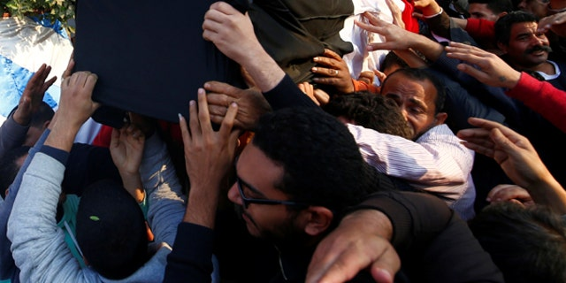 Relatives of a Christian woman who was killed in the bombing of Cairo's main Coptic cathedral, carry her body to bury at the Mokattam Cemetery in Cairo, Egypt.