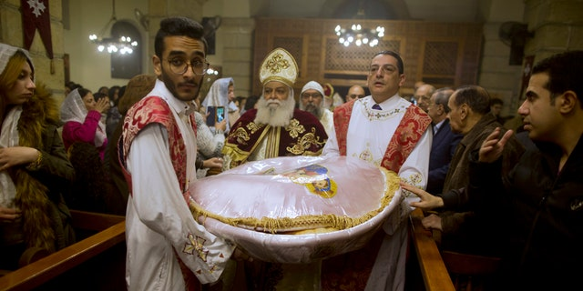 Coptic Orthodox priest, Tadros, center, carries communion bread during Christmas Eve Mass at Virgin Mary church in Cairo, Egypt, late Saturday, Jan. 6, 2018.