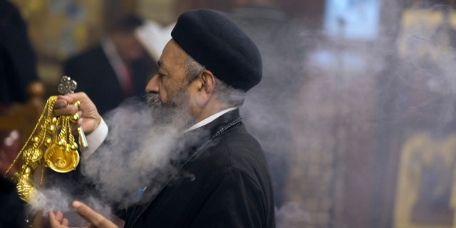 Coptic Orthodox priest, Pakhomios, spreads incense during Christmas Eve Mass at Virgin Mary church in Cairo, Egypt, late Saturday, Jan. 6, 2018.