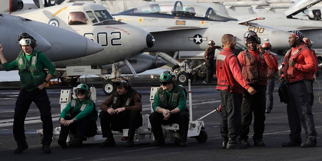 U.S. Navy sailors stand on the deck of the U.S.S. Dwight D. Eisenhower aircraft carrier on Tuesday, Nov. 22, 2016, U.S. Navy fighter jet takes off.
