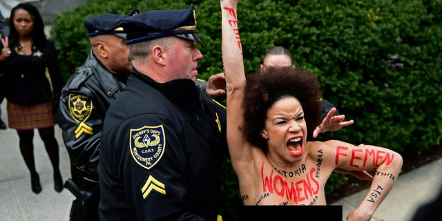 A topless protester is taken into police custody as Bill Cosby arrives at his sexual assault retrial.