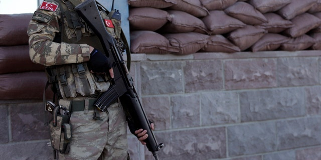 A member of the special forces stands guard outside the courthouse at the start of a trial in Ankara, Turkey.