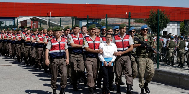 Paramilitary police and members of the special forces escort suspects of last year's failed coup in Ankara, Turkey.