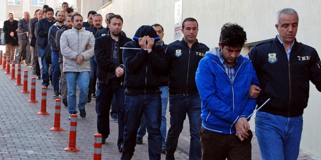 Police officers escort people, arrested because of suspected links to U.S.-based cleric Fethullah Gulen, in Kayseri, Turkey, Wednesday, April 26, 2017.