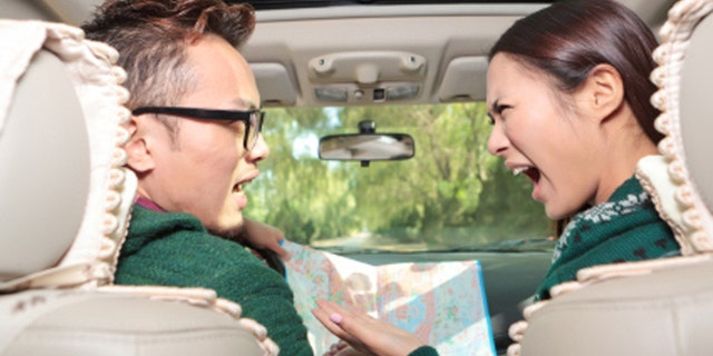 Young couple in car with map
