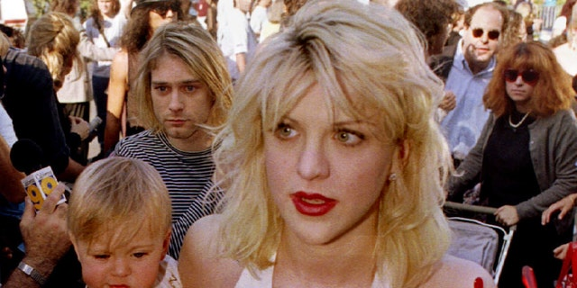 Kurt Cobain (L, behind baby), is shown as he arrives with wife Courtney Love, holding their daughter Frances Bean Cobain, for the MTV Music Awards in September 1992 in Los Angeles, Calif.