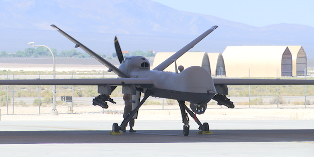 An MQ-9 Reaper drone is parked underneath a hangar on the tarmac at Creech Air Force Base.