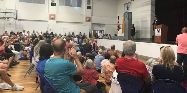 """A crowd of people filled Alma d'Arte Charter School's gymnasium Friday night to protest the president's """"zero tolerance"""" policy."""