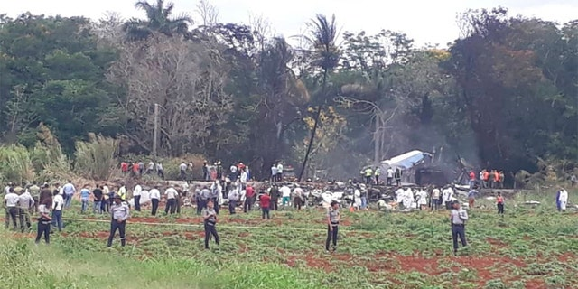 Rescue and search workers on the site where a Cuban airliner with 104 passengers on board plummeted into a yuca field just after takeoff from the international airport in Havana, Cuba on Friday.