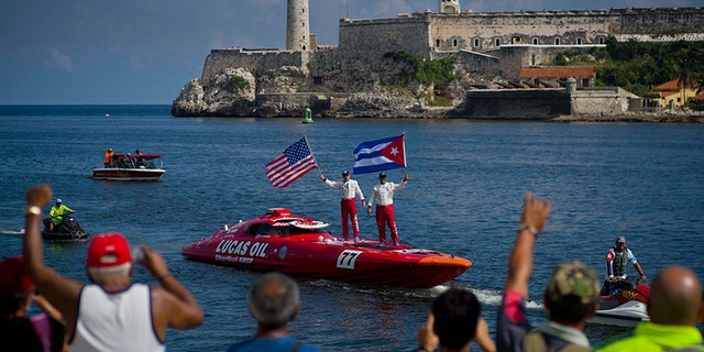 "Lucas Oil SilverHook powerboat drivers Nigel Hook, waving a Stars and Stripes, and James Johnson, waving a Cuban national flag, stand aboard their speedboat, backdropped by ""El Morro"" castle, in Havana, Cuba, Thursday, Aug. 17, 2017. The team led by Hook, a California-based businessman, is claiming a record for a powerboat crossing from Florida to Cuba. The crew reports making it from Key West to Havana on Thursday in 1 hour and 18 minutes. (AP Photo/Ramon Espinosa)"
