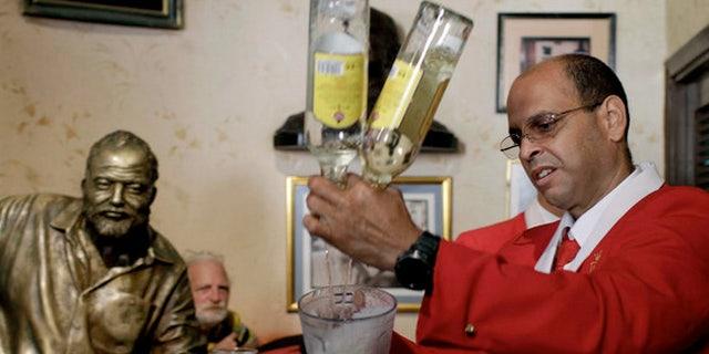 Bartender at El Floridita tavern in Havana under the bronze eye of former regular Ernest Hemingway.