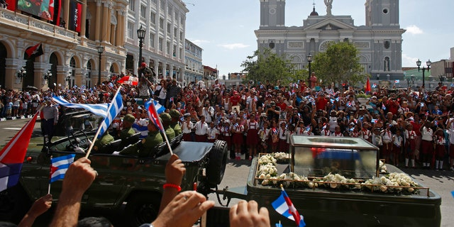 """People chant """"I am Fidel!"""" as the motorcade carrying the ashes of the late Cuban leader Fidel Castro leaves Cespedes park in Santiago, Cuba, Saturday, Dec. 3, 2016."""