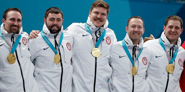 Alternate Joe Polo of the U.S. and his teammates, lead John Landsteiner, second Matt Hamilton, vice-skip Tyler George, and skip John Shuster pose with their gold medals during the victory ceremony.