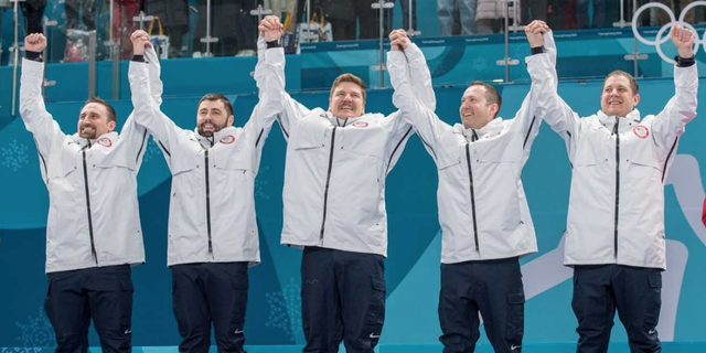 The U.S. Men's Curling team celebrates their gold medal on the podium in Pyeongchang, South Korea.