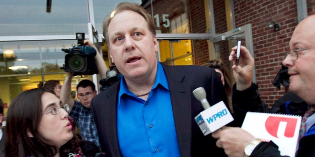 May 21, 2012: Former Boston Red Sox pitcher Curt Schilling, center, departs the Rhode Island Economic Development Corporation headquarters in Providence, R.I.