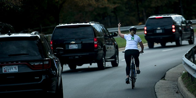 A woman on a bike gestures with her middle finger as a motorcade with US President Donald Trump departs Trump National Golf Course October 28, 2017 in Sterling, Virginia.