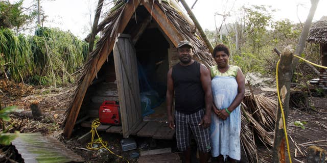 March 19, 2015: Kelson Hosea and wife Joyce Hosea stand next to the hut Kelson built to withstand Cyclone Pam.