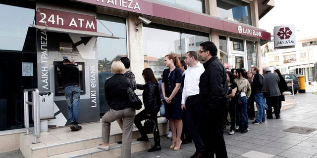 March 21, 2013: People queue at an ATM outside a closed Laiki Bank branch in capital Nicosia, Cyprus. The European Central Bank says it will keep emergency aid for Cyprus' troubled banks in place at least until Monday but will have to cut it off after that unless an international rescue program is drawn up.