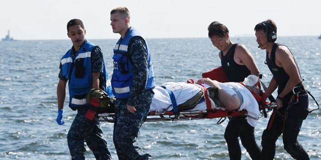 An injured USS Fitzgerald personnel is carried by U.S. military personnel, left, and Japanese Maritime Self-Defense Force members upon arriving to the U.S. Naval base in Yokosuka