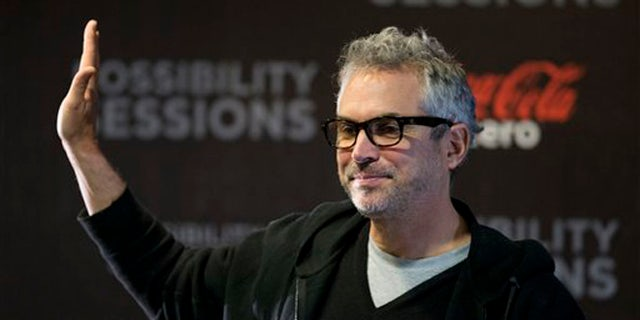 Alfonso Cuaron waves at the close of a press conference in Mexico City, Wednesday, April 30, 2014.