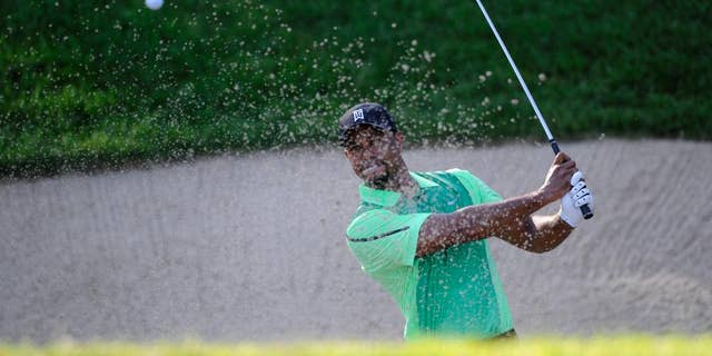 Tiger Woods hits out of a sand trap on the 10th hole during the first round of the Quicken Loans National golf tournament, Thursday, June 26, 2014, in Bethesda, Md. (AP Photo/Nick Wass)