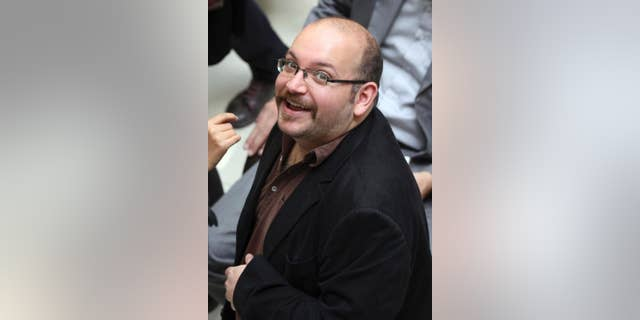 """FILE - In this photo April 11, 2013 file photo, Jason Rezaian, an Iranian-American correspondent for the Washington Post, smiles as he attends a presidential campaign of President Hassan Rouhani in Tehran, Iran. The journalist detained in Iran for months will stand trial """"soon,"""" the Islamic Republic's official news agency reported Wednesday, Jan. 28, 2015. The report by the IRNA news agency quoted Gholam Hossein Esmaeili, a senior judicial official. The report did not offer a specific time for the trial to start.(AP Photo/Vahid Salemi, File)"""
