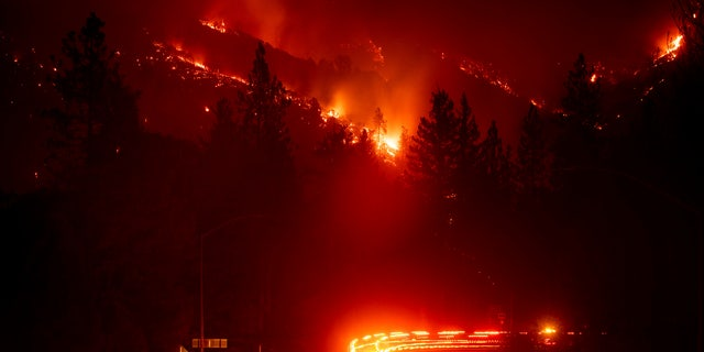 Fire trucks pass the Delta Fire burning in the Shasta-Trinity National Forest, Calif., on Wednesday, Sept. 5, 2018. Parked trucks lined more than two miles of Interstate 5 as both directions remained closed to traffic.