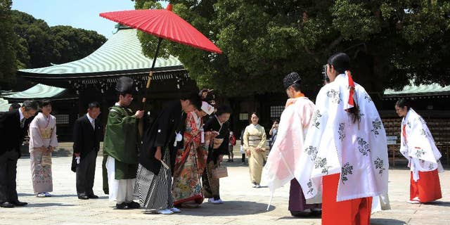 FILE - In this May 27, 2015 file photo, a newlywed couple, center, bows to a Shinto priest, third from right, in the compound of Meiji Jingu Shrine after their Japanese traditional wedding ceremony in Tokyo. In Japan, every marriage costs one surname. The Supreme Court may change that on Wednesday, Dec. 16, 2015. A Civil Code that dates from the 19th century says couples must adopt one surname, and women almost always sacrifice theirs. Five plaintiffs filed a lawsuit in 2011 saying the law is unconstitutional, violates their civil rights and puts the burden almost entirely on women. Two lower courts have ruled against them, setting the stage for Wednesday's Supreme Court ruling. (AP Photo/Eugene Hoshiko, File)
