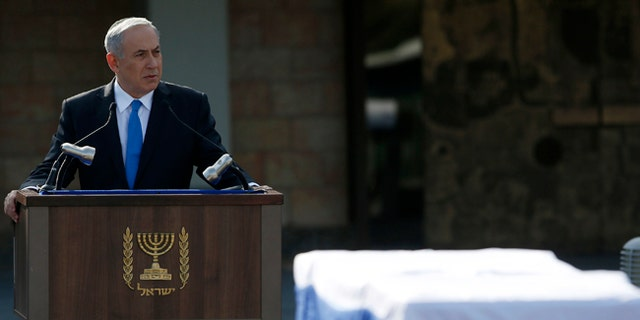 Israel's PM Benjamin Netanyahu speaks near the coffin of former PM Ariel Sharon during a memorial ceremony for Sharon in Jerusalem on Jan. 13, 2014.