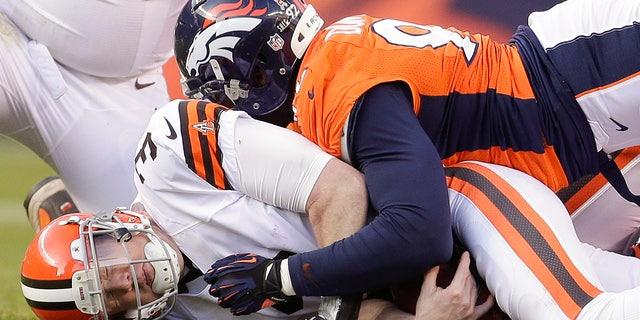 Cleveland Browns quarterback Brandon Weeden (3) is sacked by Denver Broncos defensive end Elvis Dumervil (92) in the third quarter of an NFL football game, Sunday, Dec. 23, 2012, in Denver. (AP Photo/Joe Mahoney)